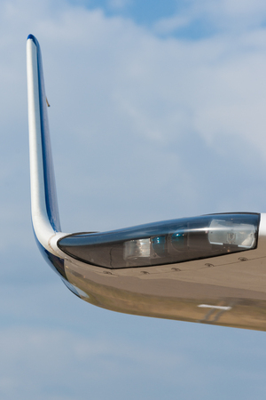 Tip of the wing of a modern civil aircraft and the wing illumination or clearance light against the background of pale blue cloudy sky 写真素材