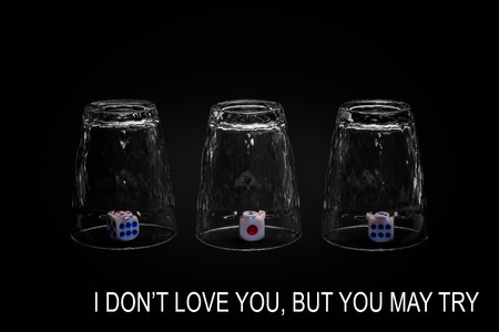 I dont love you but you may try. Closeup view of three overturned shot glasses with dices, tiles or dies inside each glass. Isolated against black background. Missing Impossible!