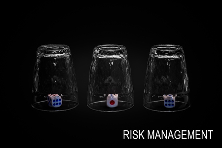 Risk management. Closeup view of three overturned shot glasses with dices, tiles or dies inside each glass. Isolated against black background. Missing Impossible!