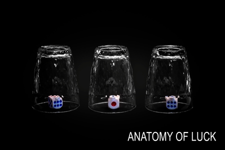 Anatomy of luck. Closeup view of three overturned shot glasses with dices, tiles or dies inside each glass. Isolated against black background. Missing Impossible! Stock Photo