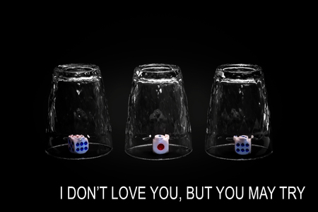 I don't love you but you may try. Closeup view of three overturned shot glasses with dices, tiles or dies inside each glass. Isolated against black background. Missing Impossible! Stock Photo - 108513263