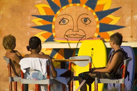 Three suntanned boogie boarder boys relaxing in front of a sunshine mural at the beach on a late summer afternoon Foto de archivo