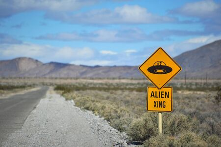 A comical traffic sign in the desert warning of alien crossing