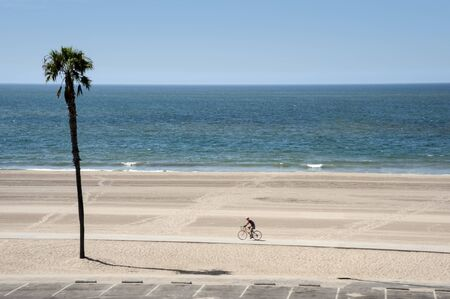 A lone bicyclist pedaling on the strand on Dockweiler Beach in Southern California Foto de archivo