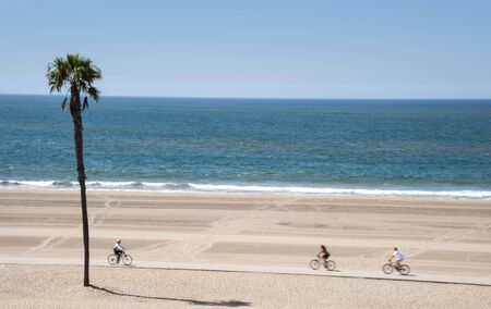 People enjoying bicycle riding on Dockweiler Beach in Southern California