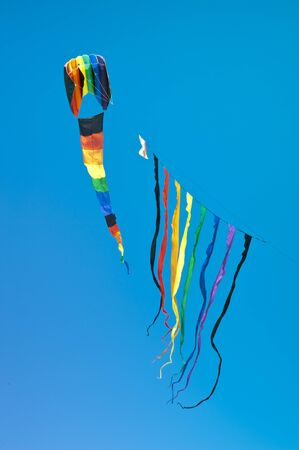 Huge rainbow-colored kite with multiple streamers isolated on a bright blue sky Foto de archivo
