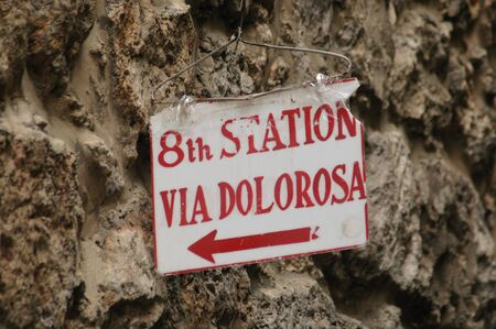 A lowly sign, hung with a wire hanger, marks the 8th Station of the Cross, Via Dolorosa
