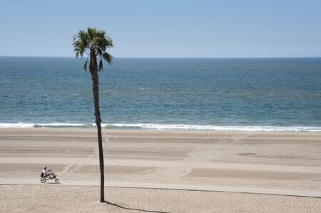An older man riding a recumbent bicycle on Dockweiler Beach in Southern California