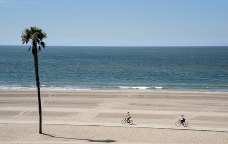 Two people enjoying bicycle riding on Dockweiler Beach in Southern California Foto de archivo