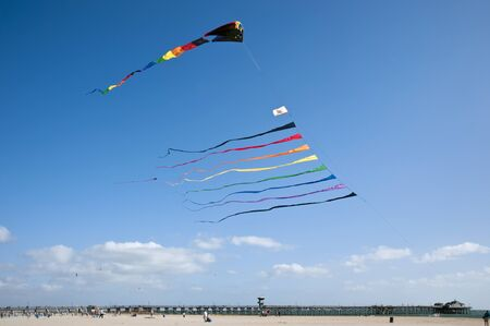 Huge colorful kite with multiple streamers on a bright blue sky sailing over the Seal Beach, California pier Foto de archivo