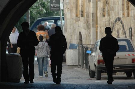 Silhouettes of schoolchildren walking through a tunnel in Jerusalem, Israel