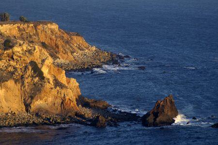 Red rocky bluff of Palos Verdes, California at dusk against a dark blue Pacific Ocean Foto de archivo