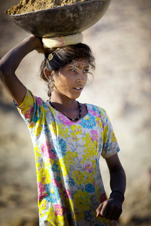 head in the sand: Indian girl carrying a basket of sand on his head shot in the state of Rajasthan in India in November 2009