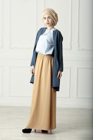 Studio photo d'une belle jeune femme de type orientale pleine longueur, sur un fond clair, habillé dans le style musulman