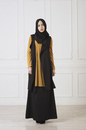 studio photo in full growth beautiful girl looks in the eastern Muslim dress and black scarf on head