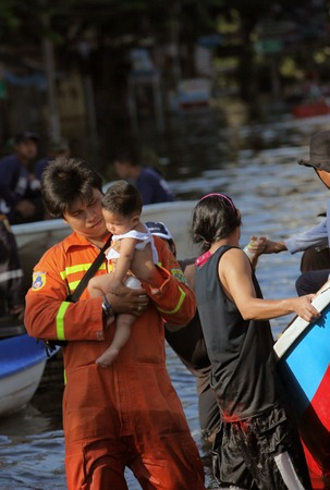 editorial: editorial photos floods in Thailand, the rescuer holding in the hands of a child, bangkok Editorial