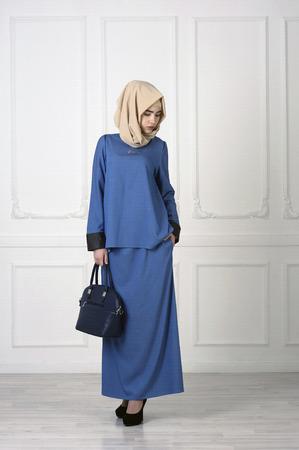 Studio photo d'une jeune femme d'apparence européenne dans un beau vêtement musulman bleu, un sac à la main et un mouchoir sur la tête, le fond classique Banque d'images