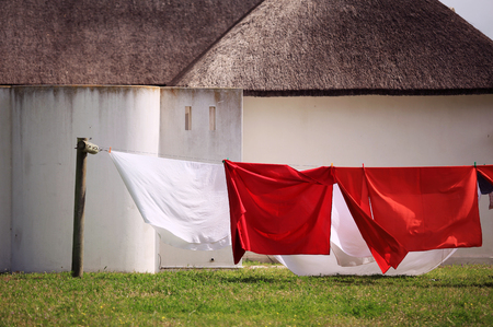 colored cloth hanging on a clothesline against white town houses with thatched roofs
