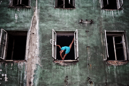 Flexible girl standing in a ballet pose in the opening windows on the facade of an old abandoned building