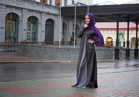 modern Muslim woman in beautiful Eastern dress standing on the background of the hotel. Ufa