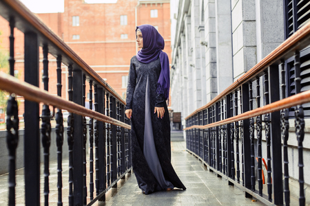modern Muslim woman in beautiful Eastern dress standing on the background of the hotel, Russia Stock Photo