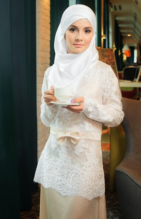 Muslim woman in a white wedding dress with a cup of tea in his hands, in a hotel 스톡 콘텐츠