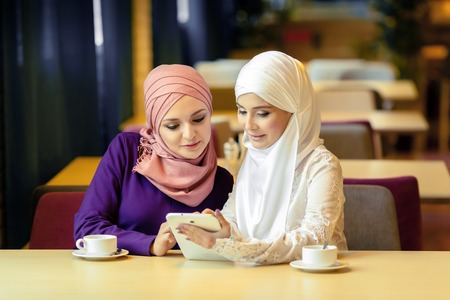 Two Muslim women in a cafe, shop online using electronic tablet, Ufa 스톡 콘텐츠
