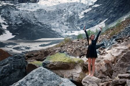 Happy young blond woman in a black dress among the huge stones on the glacier. Mestia, Georgia