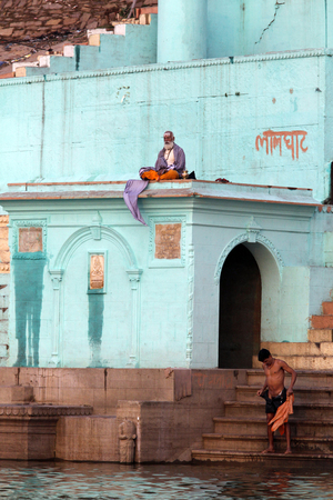 Indian monk meditating on the roof of the building and local resident washable in the river Ganges, filmed in the city varansi India in November 2009