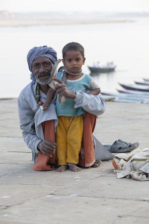 India, Varanasi - November 2009: snake charmer and a little boy posing with cobra, Ganges River