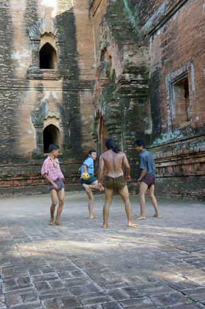 Myanmar, Pagan - 06.11.2011: Locals play with kicking ball chinlon in the popular game sepak takraw 에디토리얼