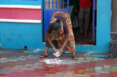 Indian woman poses flour sign Rangoli on his doorstep, filmed in the city of Rameswaram, India, in December 2013