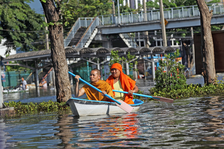 editorial photo of two Buddhist monks floating in a boat on a flooded street in Bangkok, Thailand in 2011