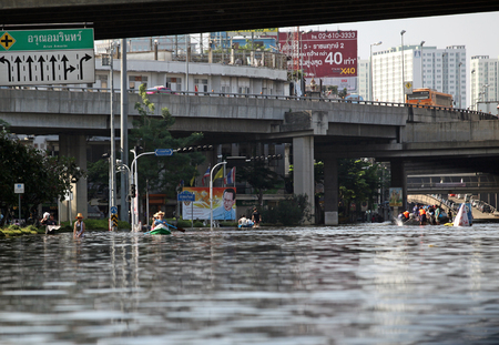 Thailand, Bangkok - November 2011: local residents moving on the water flooded the streets of the city during the flooding in Bangkok 에디토리얼