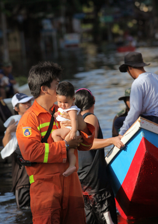 rescuer holding a baby in her arms, during a flood in Thailand