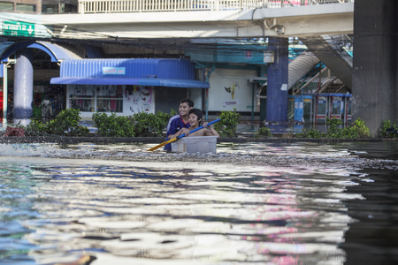 Thailand, Bangkok - November 2011:funny kids swim in a plastic box on the flooded streets