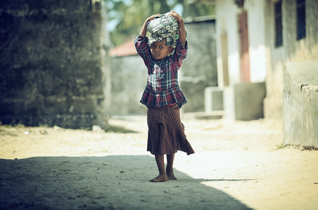 Photo Muslim girl walking barefoot on dervne with baggage on their heads, filmed in Madagascar in October 2014, Tanzania 에디토리얼