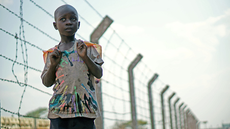 Lusaka, Zambia - September 24, 2014: African boy stands on a background of barbed wire along the railway