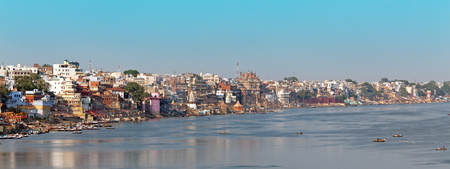 Panoramic photo of the city waterfront and the ghats of Varanasi, shot from a boat in the early morning
