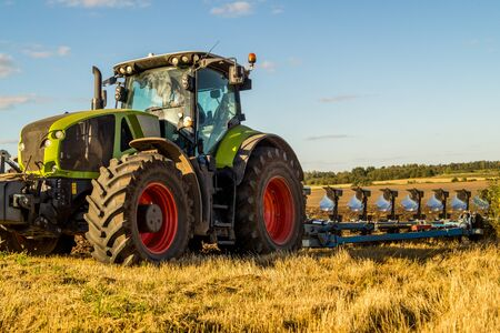 plowing: Agriculture plowing tractor on wheat cereal fields working. Stock Photo