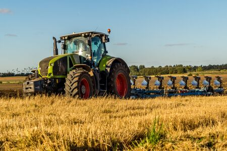 arando: Agriculture plowing tractor on wheat cereal fields working. Foto de archivo