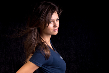 pretty brunette woman: Fashion model in photo studio isolated on black.