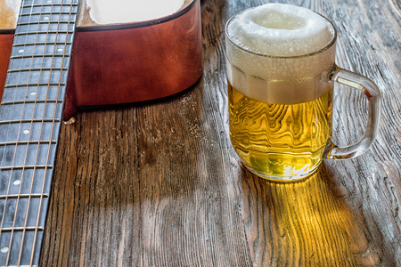 acoustic guitar and beer on an old wooden background stock photo
