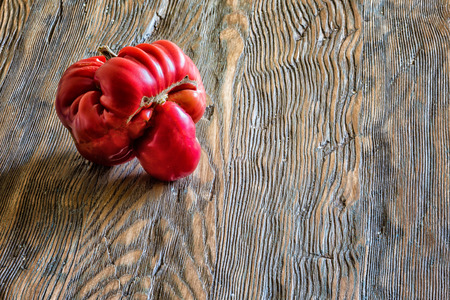 Tomato like a human head on wooden background with copy space.