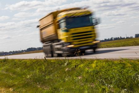 Vrachtwagenvervoer op de weg met motieonduidelijk beeld. Wazig beeld achtergrond. Kleurrijk behang met exemplaarruimte.