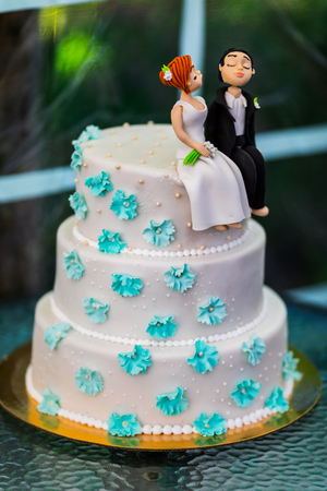 figurines: Funny figurines suite at a luxury wedding white cake. Stock Photo