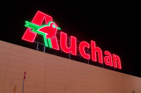 Gdansk, Poland - December 2, 2017: Illuminated Auchan logo at supermarket in Gdansk. Auchan is international supermarket chain.