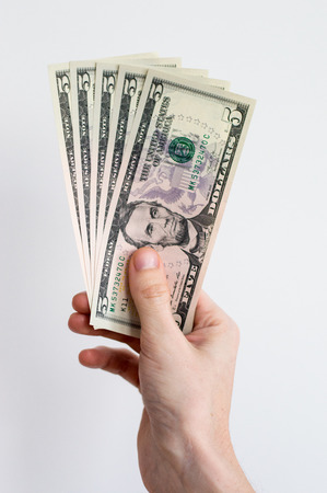 5 US dollars held in right hand. Stock Photo