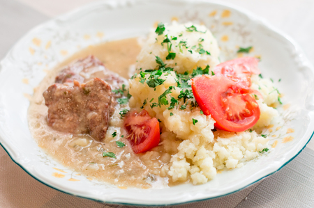 Polish traditional beef cutlets with potatoes and tomato slices. Beef cutlets knows in Poland as beekeeping.