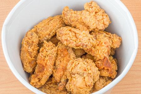 Pruszcz Gdanski, Poland - February 28, 2018: Fried chicken hot wings from KFC (Kentucky Fried Chicken) fast food.  KFC chicken hot wings in bucket of KFC.